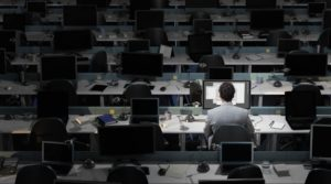 An office worker sits working in an empty office working overtime.